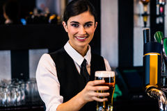 Barmaid serving a pint. In a bar stock image