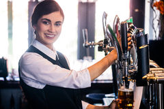 Barmaid serving a pint Royalty Free Stock Photo