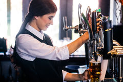 Barmaid serving a pint Royalty Free Stock Photography