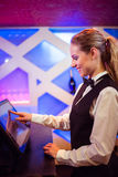 Barmaid smiling while using modern cash register Stock Images