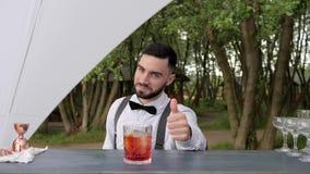 Barmanów przedstawień gest zatwierdzenie, barkeeper kciuk up, uśmiechnięty barman słuzyć whisky z lodem na baru kontuarze, lato zdjęcie wideo