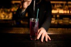 Barman ? l'aide du compte-gouttes pour faire un cocktail photographie stock