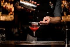 Barman à l'aide du dispositif trembleur et du tamis pour faire le cocktail images stock