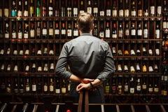 Barman à la cave complètement des bouteilles avec les boissons exquises images stock