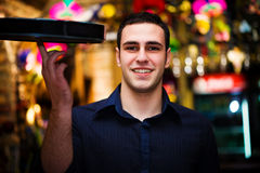 Barman. Young barmen in bar, rotates tray on a finger Stock Photos