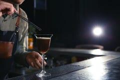 Barman adding coffee bean to martini espresso cocktail at counter, closeup. stock image