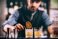 Barman adding ingredients and creating cocktail drinks on bar counter. Portrait of barman adding ingredients and creating cocktail drinks on bar counter Royalty Free Stock Image