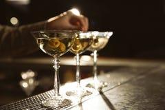 Barman adding olives to martini cocktail on counter. Space for text. Barman adding olives to martini cocktail on counter, closeup. Space for text stock image