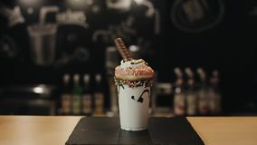 A male barista putting a chocolate wafer bar in a crazy milkshake with a donut and whipped cream. A barman adds a chocolate wafer bar to a crazy milkshake with a stock footage
