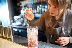Barman ajoutant l'essence au verre de cocktail à la barre Photo libre de droits