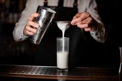 Barman ajoutant la boisson alcoolisée du dispositif trembleur en acier Photo libre de droits