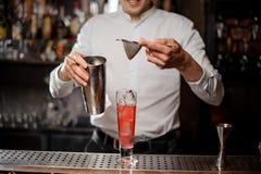 Barman ajoutant une boisson alcoolisée du dispositif trembleur en acier au travers d'un tamis Photos libres de droits