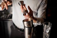 Barman ajoutant une boisson alcoolisée rouge transparente dans le dispositif trembleur en acier Photographie stock