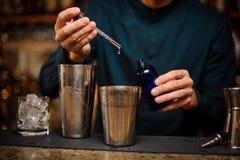 Barman ajoutant une essence à un dispositif trembleur en acier avec un cocktail alcoolique Images stock