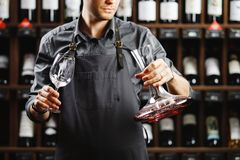 Barman in apron holds vessel with red wine and glass. Barman in apron holds big decanter with red wine on bottom and glass, stands in cellar among sealed bottles Royalty Free Stock Images