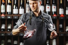 Barman in apron holds vessel with red wine and glass. Barman in apron holds big decanter with red wine on bottom and glass, stands in cellar among sealed bottles Stock Photos