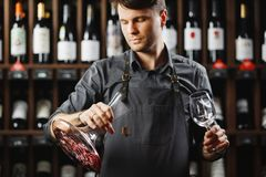 Barman in apron holds vessel with red wine and glass. Barman in apron holds big decanter with red wine on bottom and glass, stands in cellar among sealed bottles Stock Image