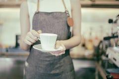 Barman asiatique de femmes tenant une tasse de café - travailleuse active smal photos stock