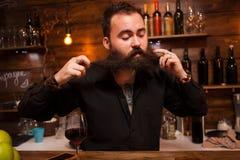 Barman attirant jouant avec sa longue barbe derri?re le compteur photos libres de droits