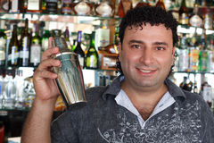 Barman avec le dispositif trembleur derrière l'armoire de bar. Photos stock