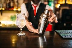 Barman avec le dispositif trembleur derrière un compteur de barre Image stock