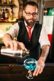 Barman avec le dispositif trembleur faisant le cocktail d'alcool Photographie stock