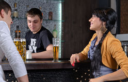 Barman ayant une vie sociale avec des clients à la barre Image libre de droits