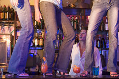 Barman baillant à trois jeunes femmes dansant sur le bar Photo libre de droits