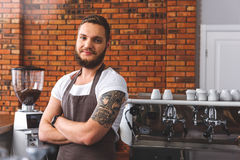 Barman barbu joyeux travaillant dans le café photo stock