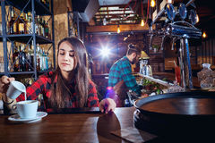 The barman barista`s girl makes coffee on the bar royalty free stock photography