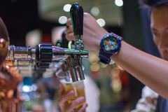 Barman or bartender pouring a draught lager beer from beer tap Stock Photos