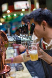 Barman or bartender pouring a draught lager beer from beer tap Stock Photography