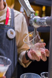 Barman or bartender pouring a draught lager beer from beer tap Stock Images