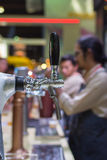 Barman or bartender pouring a draught lager beer from beer tap Stock Image