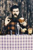 Barman with beard and blinking face holds glass with drinking straw cocktail. Man shows ok gesture on wooden texture. Background. Delicious cocktails concept royalty free stock photography