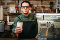 Barman in black apron stretches plastic cup. Of coffee in hands Stock Photos