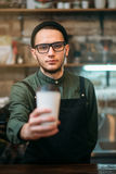 Barman in black apron stretches plastic cup. Of coffee in hands Royalty Free Stock Photos