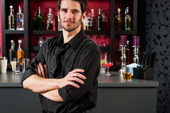 Barman in black standing at cocktail bar Royalty Free Stock Photos