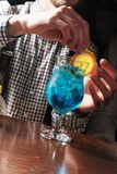 Barman in a blue shirt pours from a shaker into a glass of alcohol cocktail Blue Lagoon on a dark background in the bar royalty free stock photo