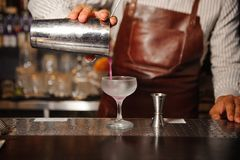 Barman in a brown apron pours from a steel shaker alcohol cocktail. Barman in a brown apron pours from a steel shaker into a crystal glass a lilac-colored stock photography