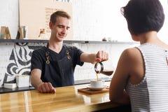 Barman causant avec l'invité et le café servant photos stock