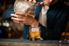 Barman châtain versant une boisson alcoolisée dans un verre avec un glaçon photographie stock