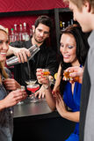 Barman cocktail shaker friends drinking at bar. Barman making cocktail for young friends at the bar stock photography