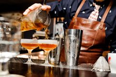 Barman completes the preparation of two alcoholic cocktails using bar equipment. Barman in a blue shirt and brown apron completes the preparation of two Stock Photography
