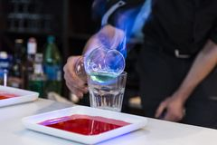 Burning cocktail. The barman is cooking a burning cocktail stock images