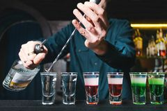 The barman creates alcoholic shots at the bar at the restaurant. The barman pours alcohol into shots. Royalty Free Stock Photos