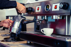 Barman cuisant le lait à la vapeur à la machine de café Photographie stock