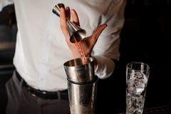Barman dans la chemise blanche ajoutant une boisson alcoolisée rouge transparente dans le dispositif trembleur en acier Images libres de droits