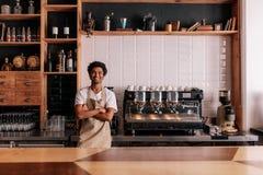 Barman dans le tablier regardant l'appareil-photo et le sourire image libre de droits