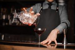Barman dans un lien et un tablier versant la boisson alcoolisée rouge dans un verre de cocktail Photos libres de droits